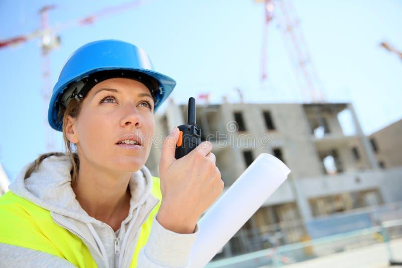 Tekniker för ung kvinna som arbetar på byggnadsplats royaltyfria foton