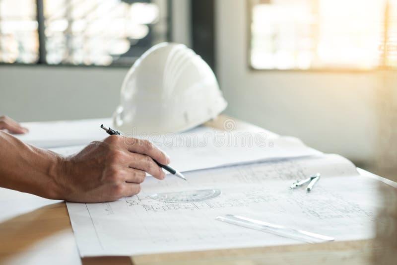 Tekniker Hand Drawing Plan för person` s på blått tryck med arkitekten royaltyfria bilder