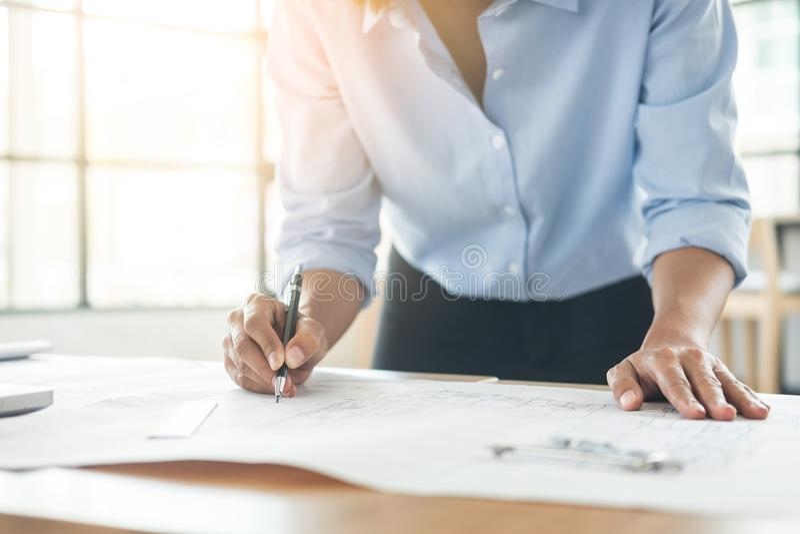 Tekniker Hand Drawing Plan för person` s på blått tryck med arkitekten arkivbild