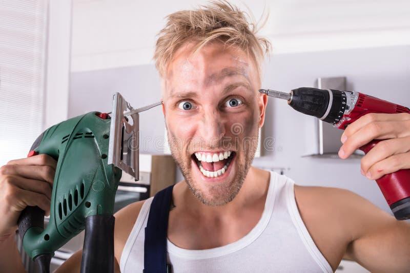 Tekniker Holding Electric Drill och skruvmejsel på hans huvud royaltyfri bild