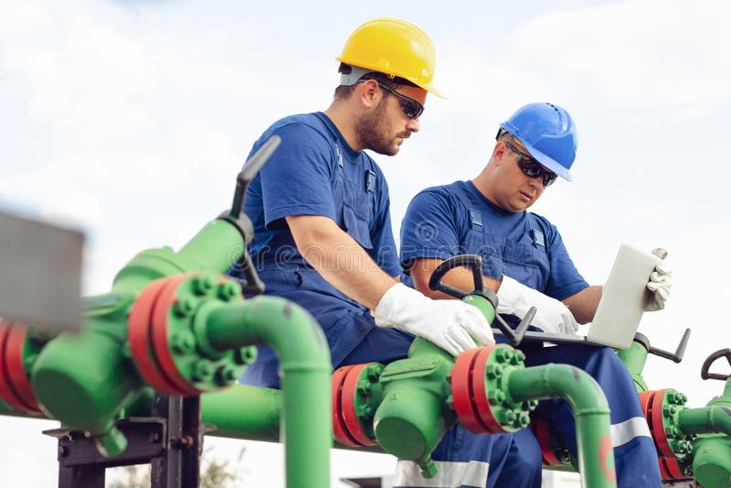 Tekniker i det olje- och naturgasfältet, rörledning, raffinaderi arkivfoto