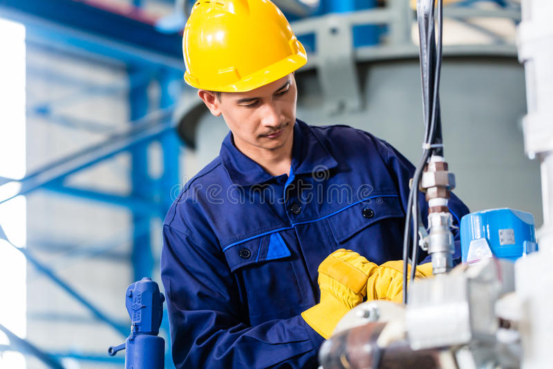 Tekniker i fabrik på maskinunderhåll royaltyfria foton