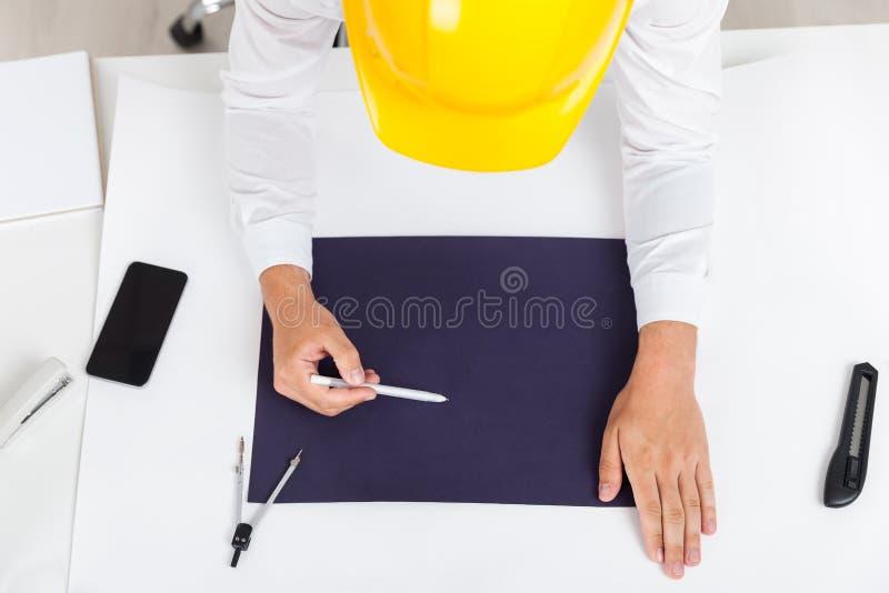 Tekniker i gul hjälmteckningsritning arkivfoto