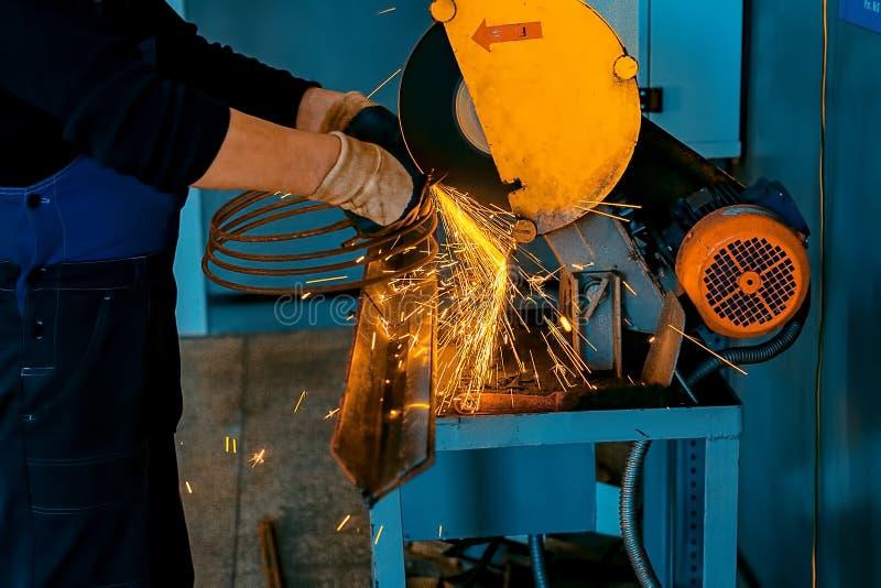 Tekniker i handskar och overaller i arbetsplatsen Klippa metall med en maskin i shoppa royaltyfri bild