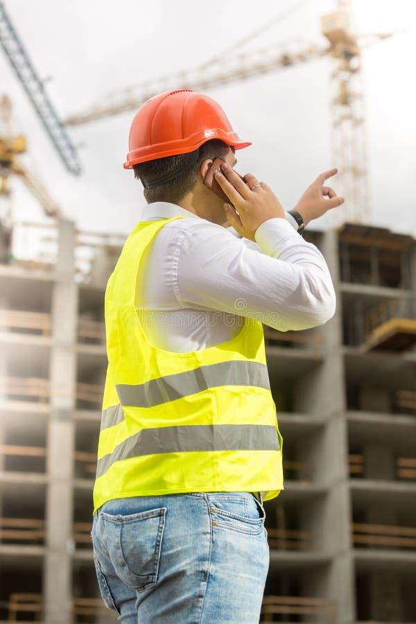 Tekniker i hardhat som talar vid telefonen och pekar på byggnadssi arkivbild
