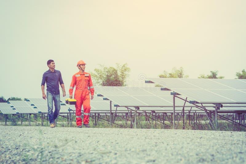 tekniker i solenergiväxten som arbetar på installation av solpanelen royaltyfri foto