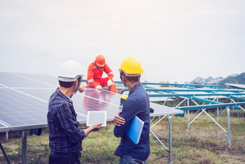 tekniker i solenergiväxten som arbetar på installation av solpanelen royaltyfria bilder