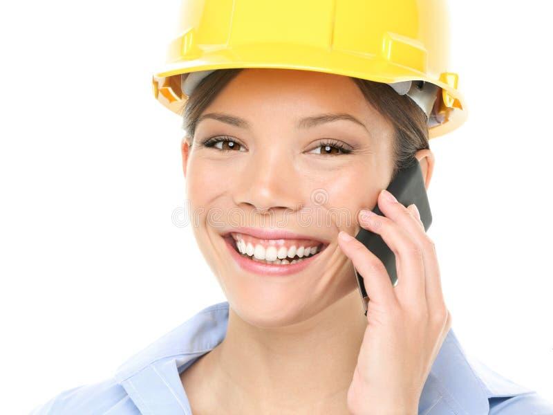 Tekniker - kvinna med hardhaten på mobiltelefonen royaltyfri fotografi