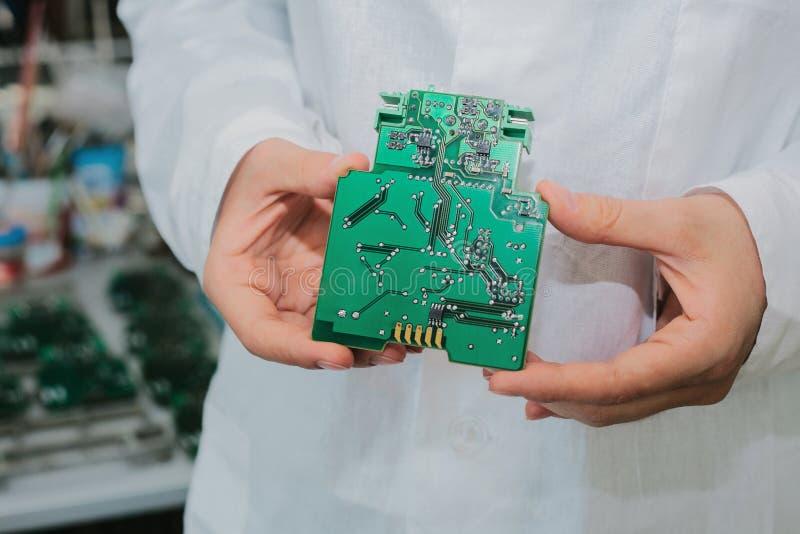 Tekniker med datorströmkretsbrädet med chiper Reservdelar och delar för datorutrustning Produktion av royaltyfria foton