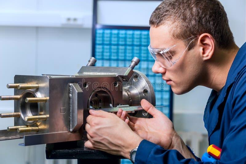 Tekniker med en klämma som mäter apparaten i den moderna laboratoren royaltyfri bild