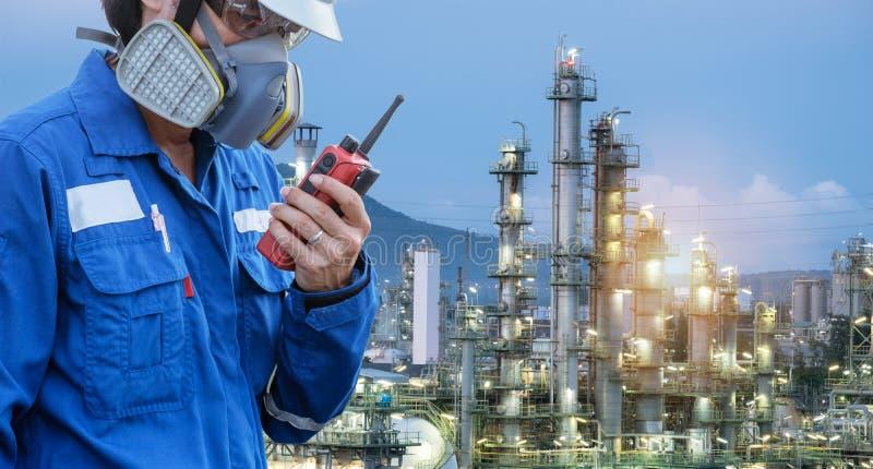 Tekniker med petrokemisk gasmask- och walkietalkieagainst royaltyfri foto