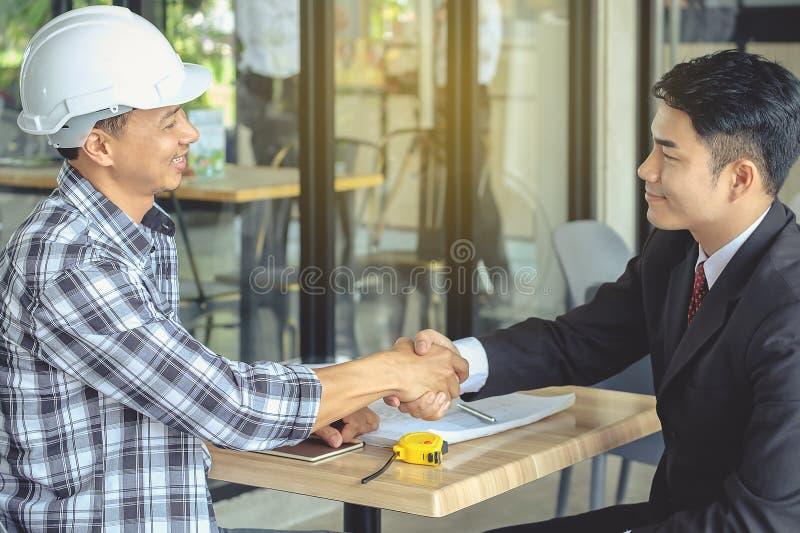 Tekniker- och affärsmanhandskakningöverenskommelse i förhandlingar in fotografering för bildbyråer