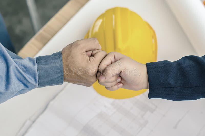 Tekniker- och affärsmanhandskakning, teamwork mellan yrkesmässiga konstruktionsteknikerer efter det färdiga projektet arkivbilder