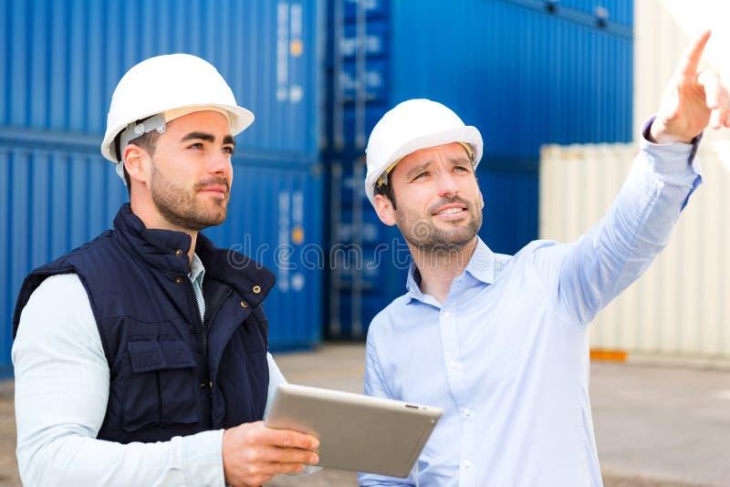 Tekniker och arbetare som talar om arbete på skeppsdockan arkivbilder