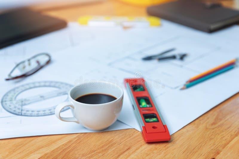 Tekniker- och arkitektbegrepp, Closeupkaffe på skrivbordet med ritningar royaltyfria foton