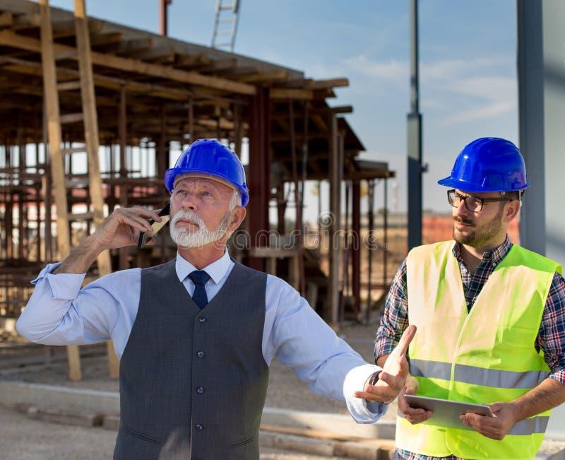 Tekniker och byggnadsarbetare på byggnadsplatsen royaltyfria foton