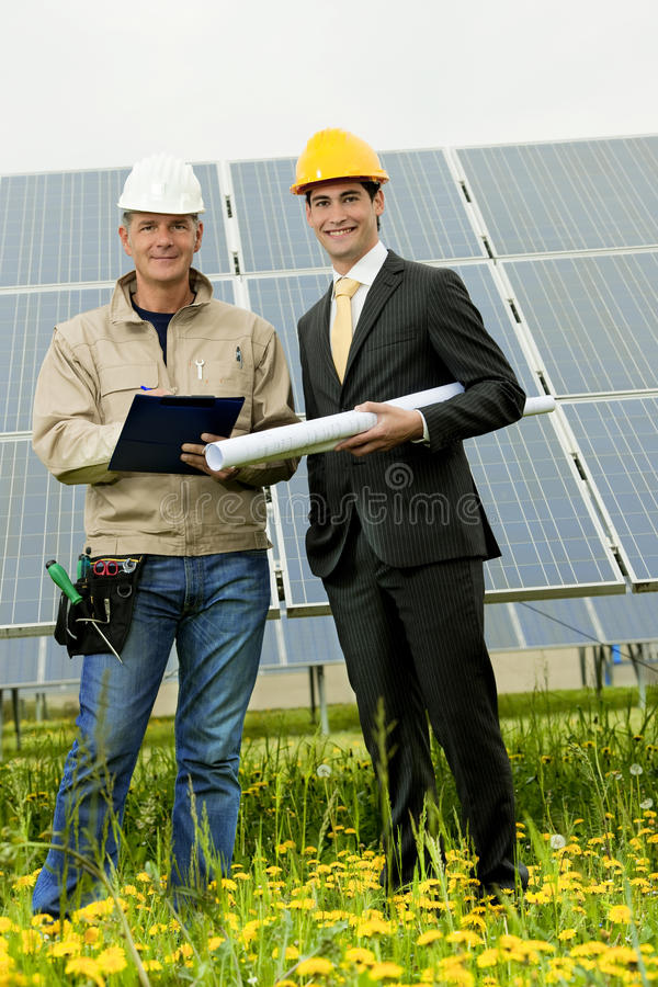 Tekniker och tekniker på den sol- strömstationen royaltyfria bilder