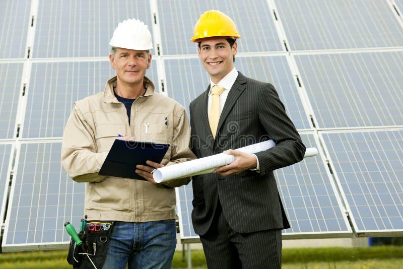 Tekniker och tekniker på den sol- strömstationen arkivfoton