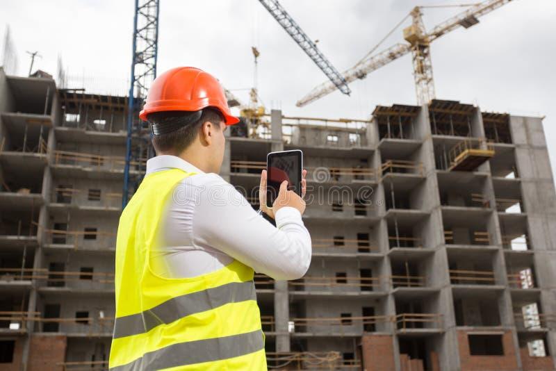 Tekniker på byggnadsplats med den digitala minnestavlan arkivfoton