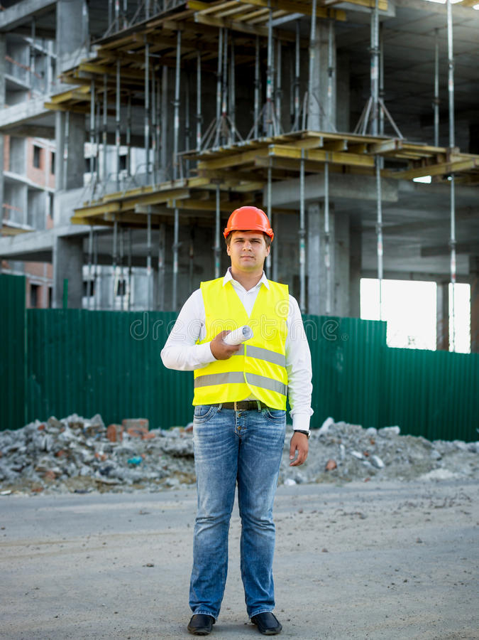 Tekniker på konstruktionsplatsen som poserar mot materialet till byggnadsställning arkivfoto