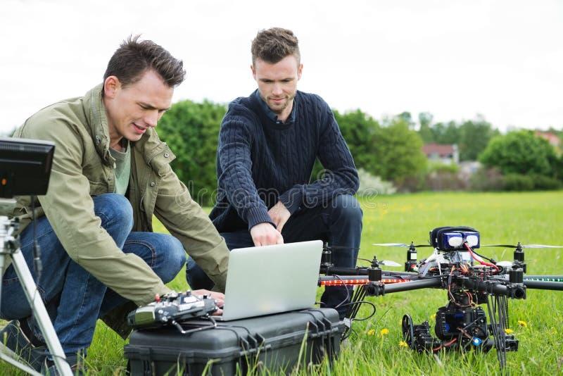 Tekniker som använder bärbara datorn med UAV-surret royaltyfria bilder