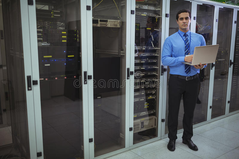 Tekniker som använder bärbara datorn, medan analysera serveren arkivbilder