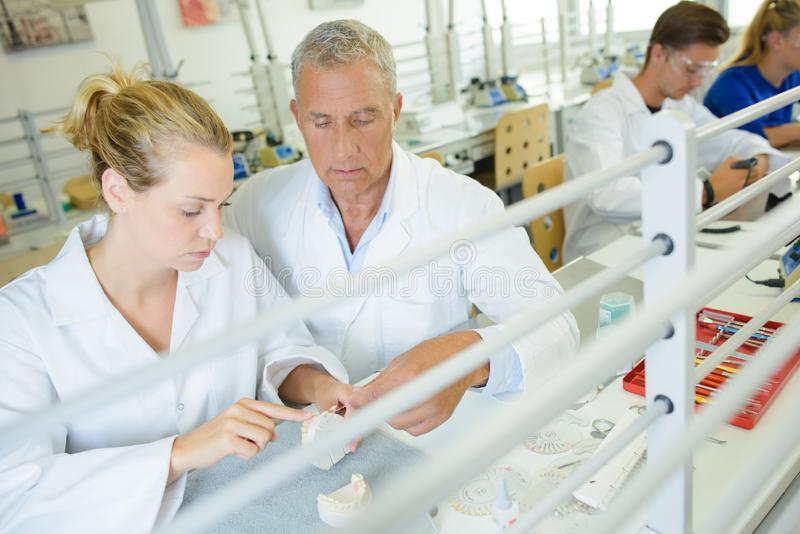 Tekniker som arbetar i tand- laboratorium royaltyfri bild