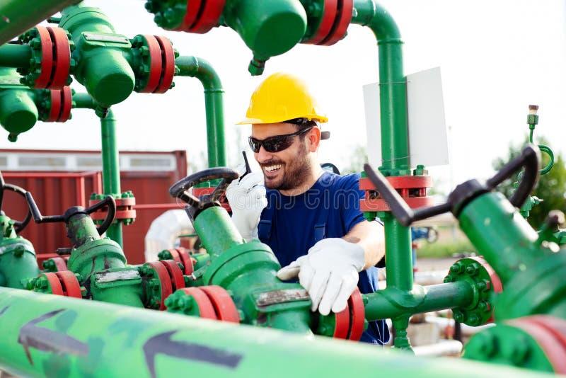 Tekniker som arbetar med rörledningstyrning inom fossila bränslenraffinaderi royaltyfria bilder
