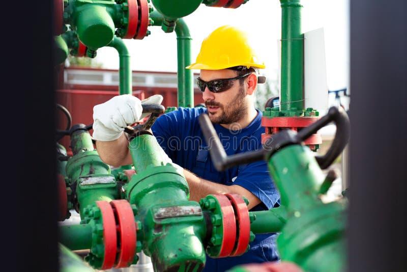 Tekniker som arbetar med rörledningstyrning inom fossila bränslenraffinaderi royaltyfri foto