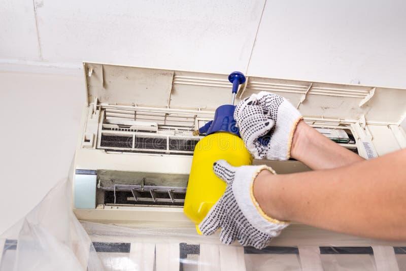 Tekniker som besprutar kemiskt vatten på luftkonditioneringsapparatraster till royaltyfri foto