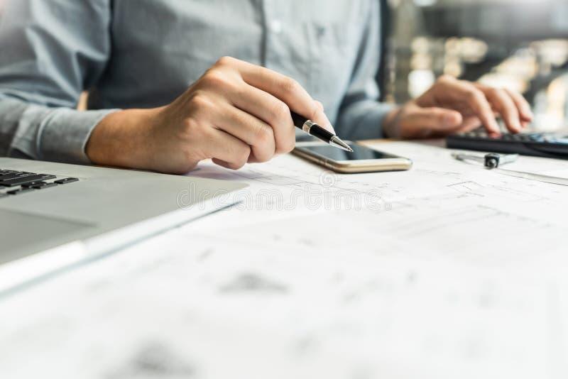 Tekniker som drar ett blått tryck för att godkänna designbyggnad med arkitektutrustning på arbetande byggnad för kontorstabellkon royaltyfria foton