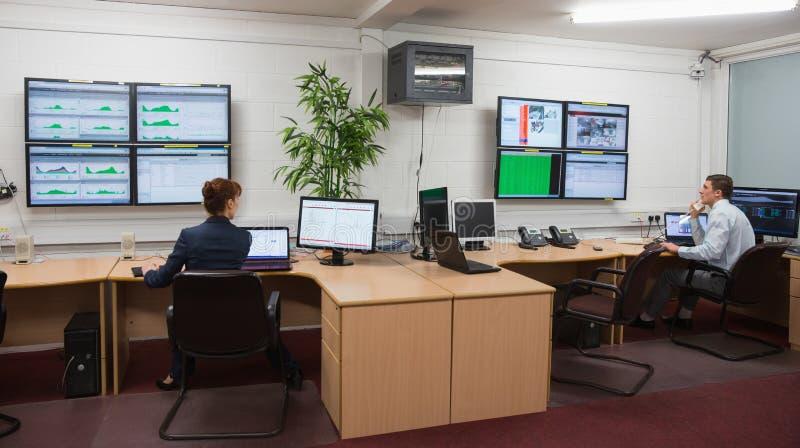 Tekniker som i regeringsställning sitter körande diagnostik arkivfoton