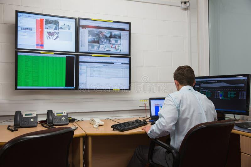 Tekniker som i regeringsställning sitter körande diagnostik arkivbild