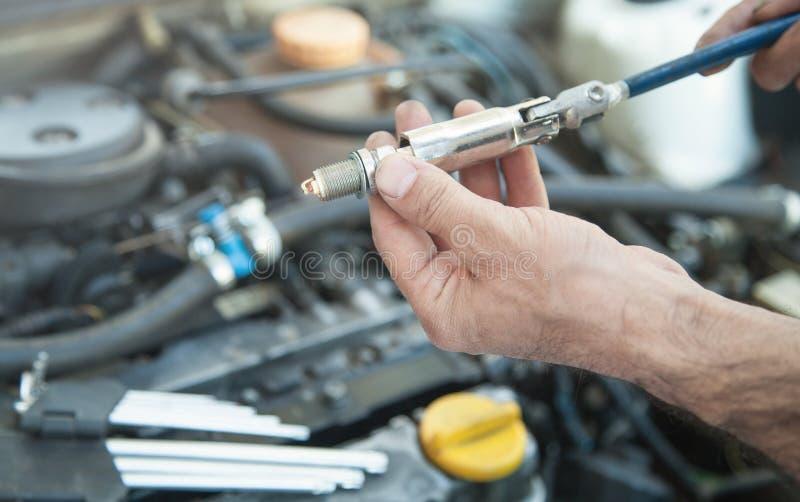 Tekniker som installerar den nya stearinljuset i bilmotor royaltyfri foto