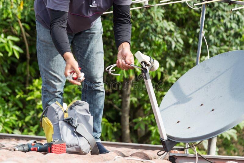 Tekniker som installerar den satellit- maträtten och televisionantennen på taköverkant arkivbild
