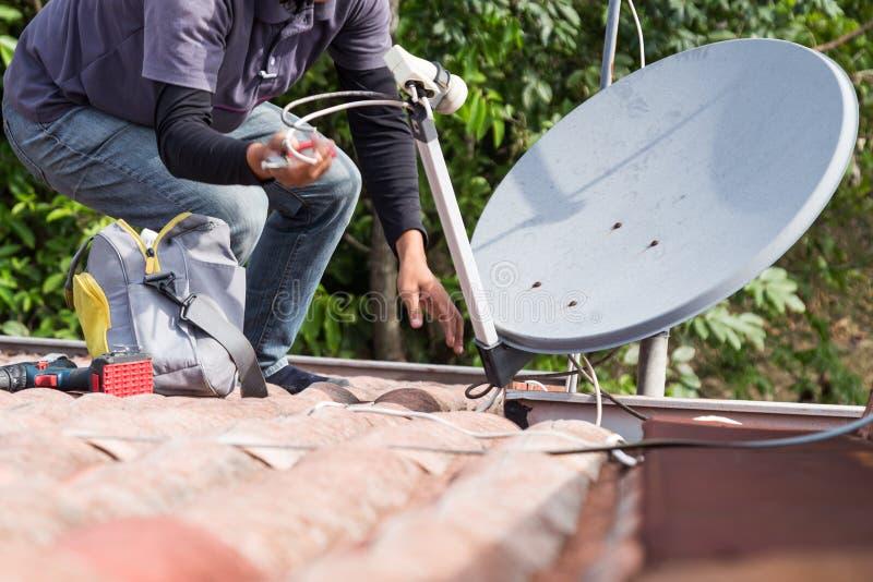 Tekniker som installerar den satellit- maträtten och televisionantennen på taköverkant royaltyfri bild