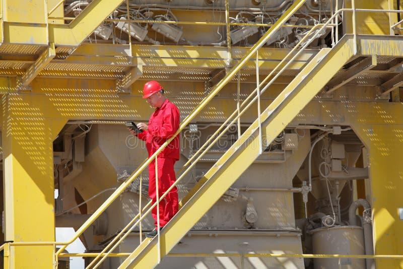 Tekniker som kontrollerar industriell process arkivbild