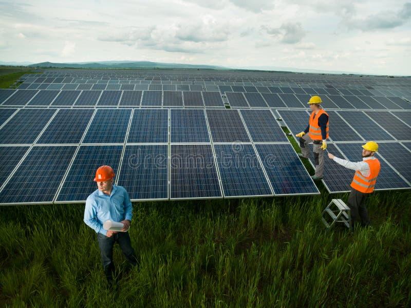 Tekniker som kontrollerar solpanelstationen royaltyfri bild