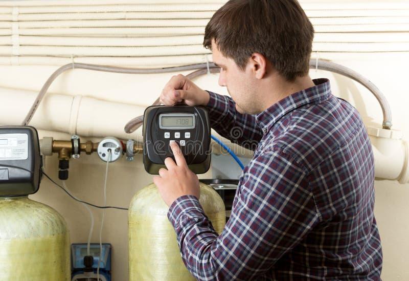 Tekniker som kontrollerar tryckmeter på fabriken royaltyfri foto