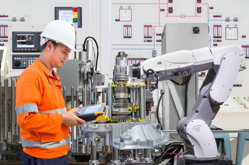 Tekniker som programmerar robotic bransch i bilindustri royaltyfria foton