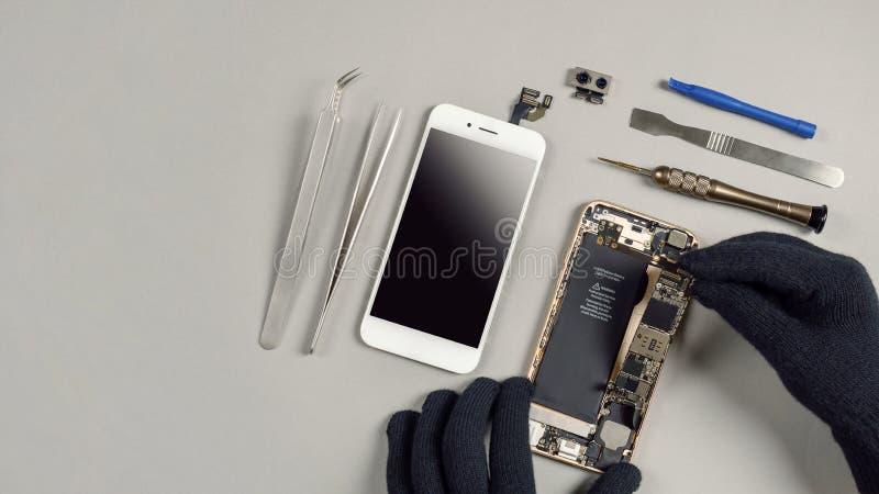Tekniker som reparerar den brutna smartphonen på skrivbordet arkivbilder