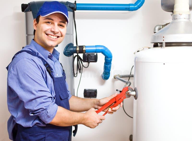 Tekniker som reparerar en hot-water värmeapparat arkivfoton