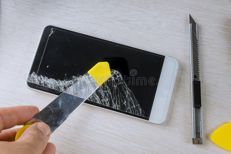 Tekniker som reparerar smartphonen f?rbi i den elektroniska reparera teknologin f?r mobiltelefon arkivfoton