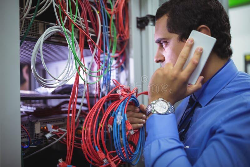 Tekniker som talar på mobiltelefonen, medan att kontrollera kablar royaltyfri bild