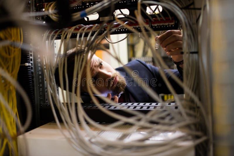 Tekniker som talar på mobiltelefonen, medan att kontrollera kablar arkivfoton