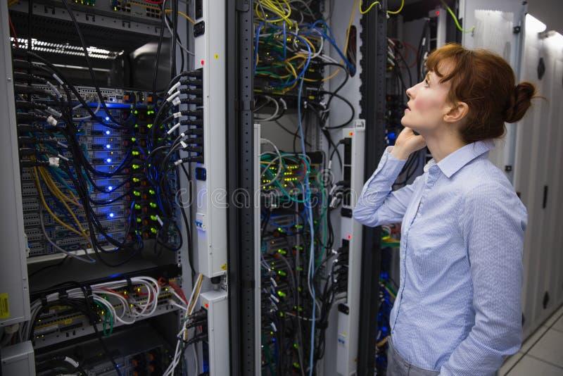 Tekniker som talar på telefonen, medan analysera serveren arkivfoton