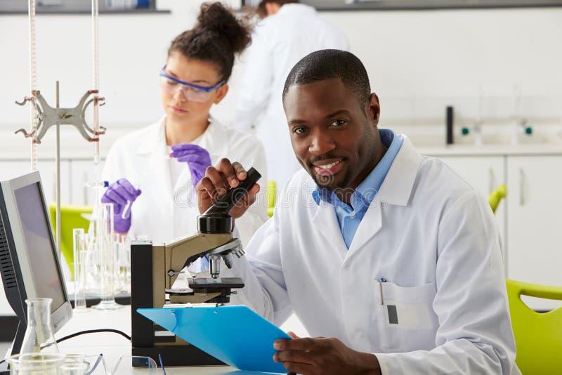 Tekniker som ut bär forskning i laboratorium arkivbilder