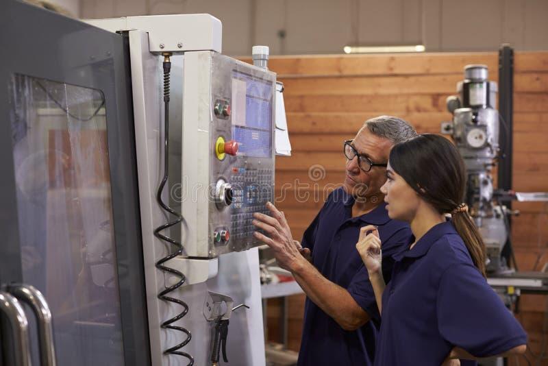Tekniker Training Female Apprentice på CNC-maskinen arkivbilder