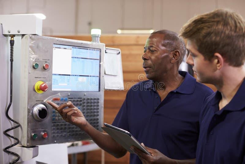 Tekniker Training Male Apprentice på CNC-maskinen royaltyfri bild