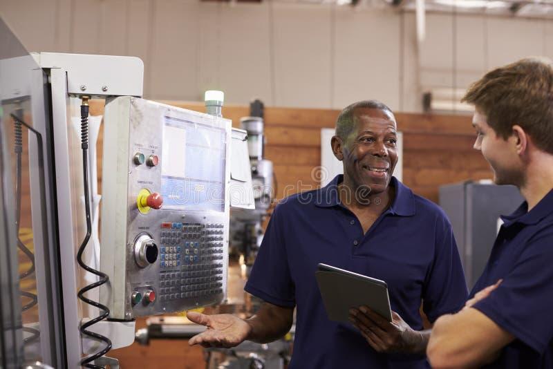 Tekniker Training Male Apprentice på CNC-maskinen royaltyfri fotografi